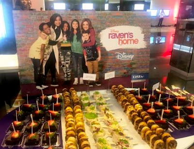 Eats at Disney Raven's Home Premiere with poster at back