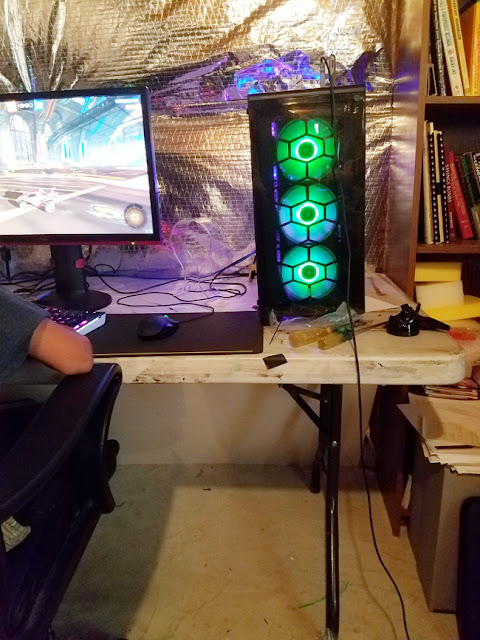 boy playing video games on pc in the basement.