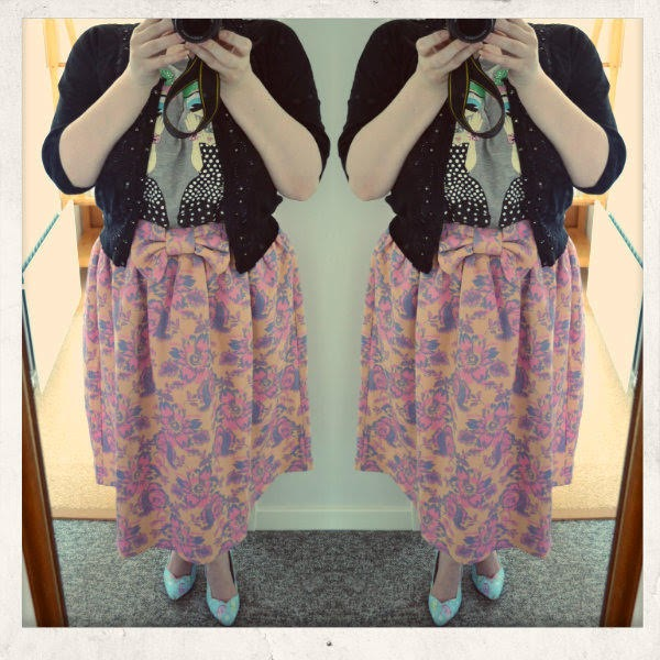 Plus size blogger wearing floral skirt, girl tshirt and black cardigan with mermaid shoes