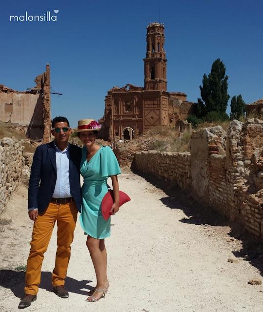 Invitada boda con chistera con la iglesia de Belchite de fondo