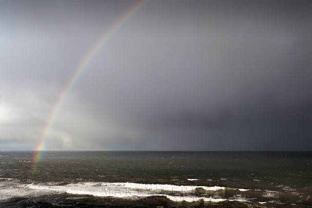 Stormy afternoon on the Leas as a rainbow forms over the ocean.