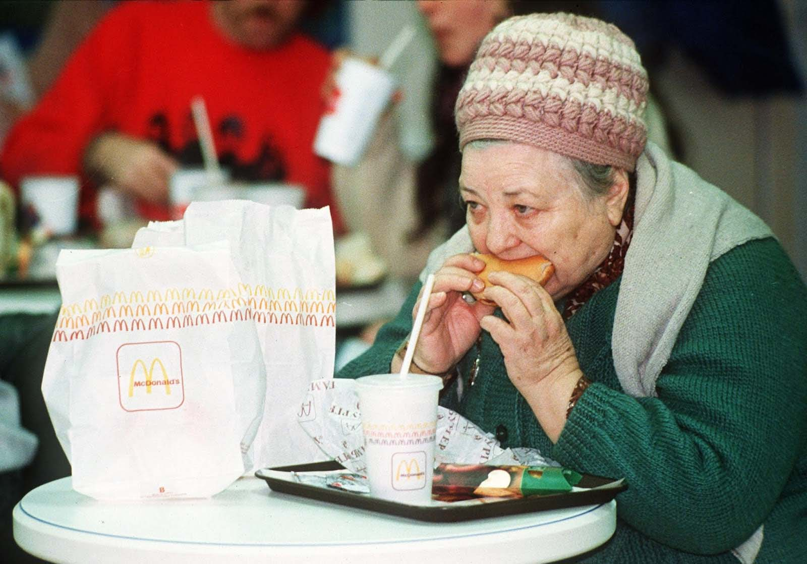 An old lady enjoyed her burger.