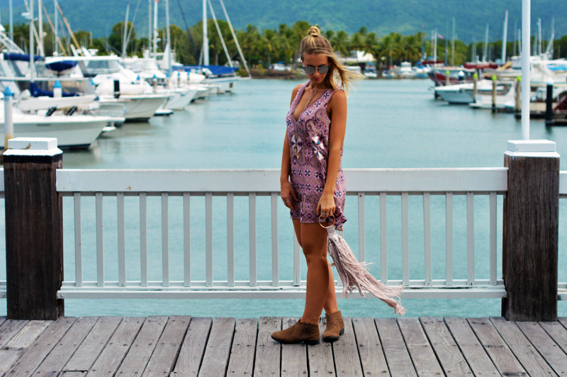 blonde girl wearing summer outfit boho print mauve dress fringe clutch ankle boots festival outfit