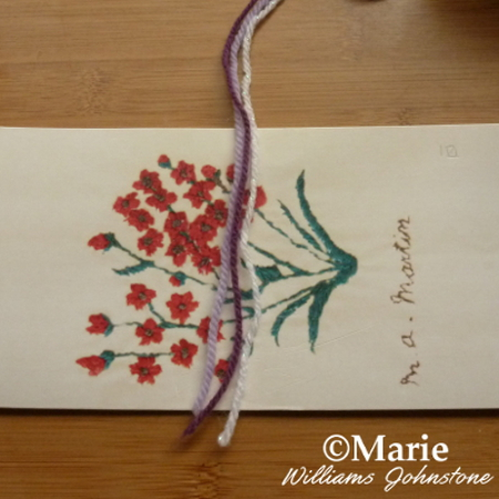 Strands of yarn wool laid over a piece of card ready to start making tassels begin easy simple method