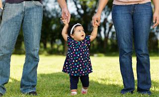 Parents walking baby with hands held