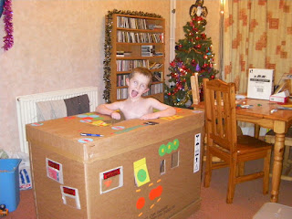 boy in cardboard shipping container, pallet-sized