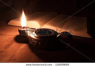 Αναμμένο λυχνάρι δίπλα σε ανοιχτό βιβλίο