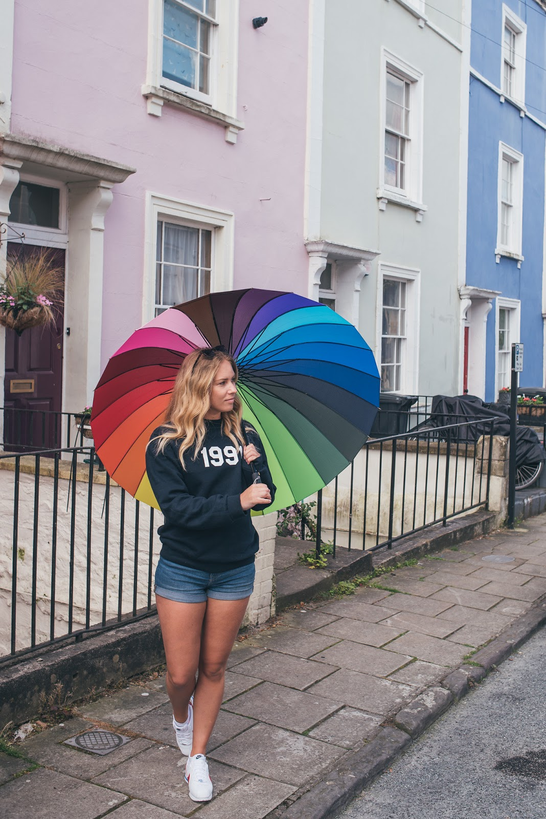 Rachel Emily with Rainbow Umbrella in front of Pastel Rainbow Houses