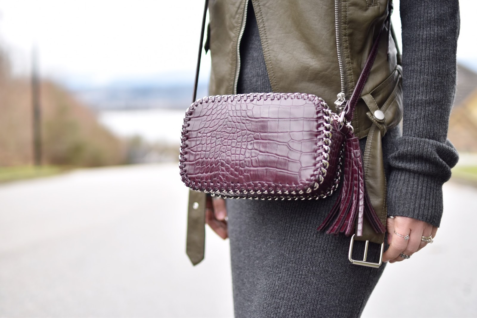 Monika Faulkner outfit inspiration - turtleneck sweater dress, motorcycle vest, cross-body bag