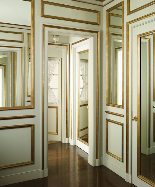 hallway of doors and mirrors with mint walls and gold decorative molding