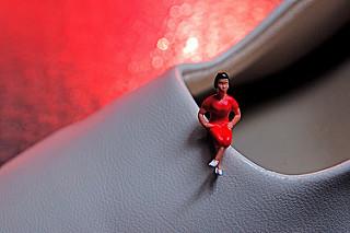 Muñequita diminuta con vestido rojo sentada en el borde de un zapato blanco