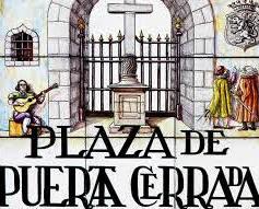 Típicos azulejos pintados conforman una placa en la que destacan una puerta de piedra cerrada por verja de hierro, y delante una cruz de piedra.