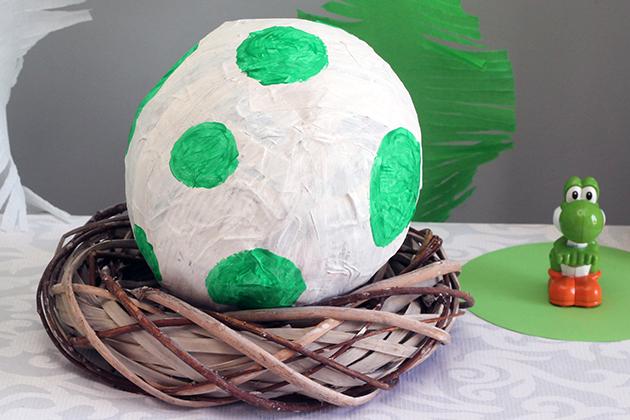 Dit Yoshi-ei van papier mache is heel gemakkelijk te maken. Wat je nodig hebt: een ballon, krantenpapier (repen 3 cm breed), water (2 delen), bloem (1 deel) en witte en groene verf. De hele ballon volplakken, maar bij het tuutje een gat openhouden. Een paar uur laten drogen (eventueel met behulp van een föhn) en dan nog een laag toevoegen. Nachtje laten drogen en de volgende dag ballon lek prikken en het ei twee maal met witte verf beschilderen. Eenmaal droog de groene stippen er op schilderen. Krans van de Action als nest. Natuurlijk ook erg leuk als pinata!