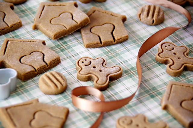 Homemade Christmas dog treats shaped like gingerbread men and dog houses