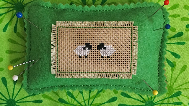 Lambs cross-stitched on felt pincushion