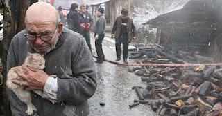 83χρονος αγκαλιάζει την γάτα μπροστά από τα ερείπια του καμένου σπιτιού του