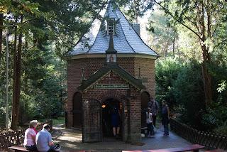 Eine kleine Kapelle steht im Wald. Das schmiedeeiserne Tor ist geöffnet und Leute stehen vor und in der Kapelle.