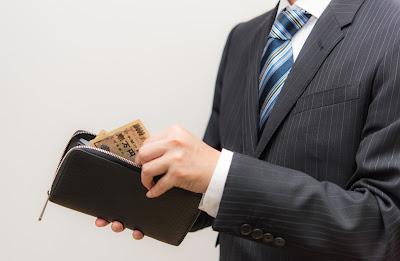 スーツを着た男性が財布からお札を出す