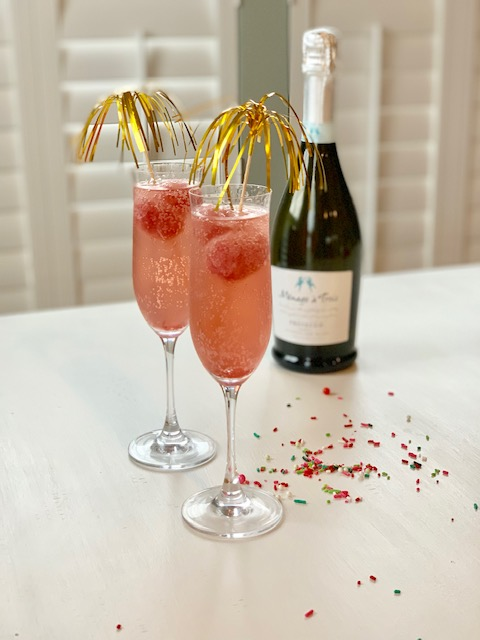A bottle of champagne and two very pretty cocktails in champagne glasses.
