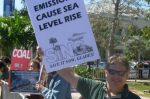 "Protester holds ""Emissions Cause Sea Level Rise"" sign (Photo Credit: Coalswarm)"