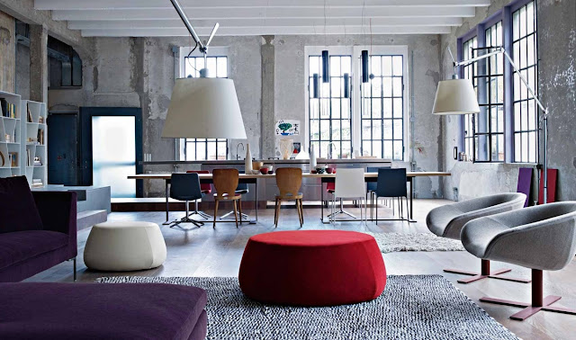 Unfinished concrete walls and wooden floors provide an industrial canvas for bold.