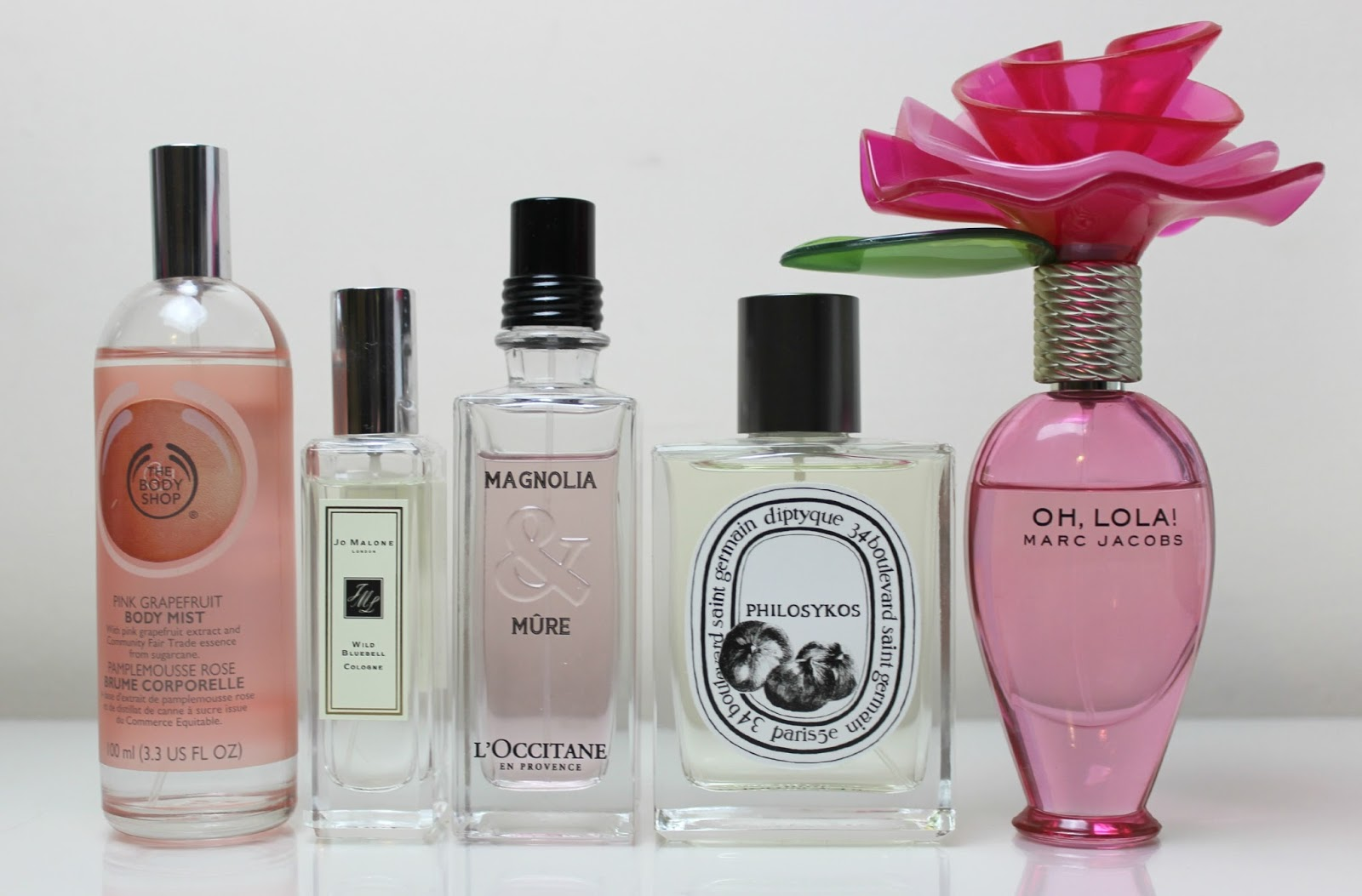 A picture of The Body Shop Pink Grapefruit Body Mist, Jo Malone Wild Bluebell, L'Occitane Magnolia & Mure, Diptyque Philosykos and Marc Jacobs Oh Lola!