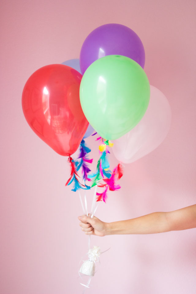 Decorate plain balloon strings with feathers - so pretty!