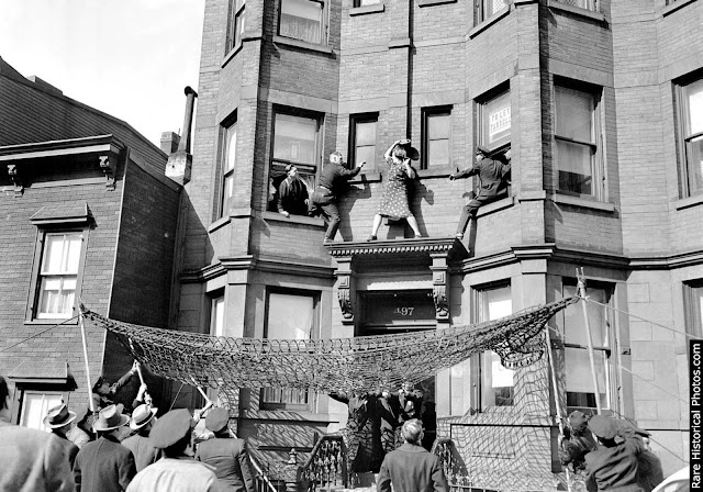 Edna Egbert fights with police as they try to prevent her from jumping off the second-story ledge of her home at 497 Dean Street in Brooklyn.