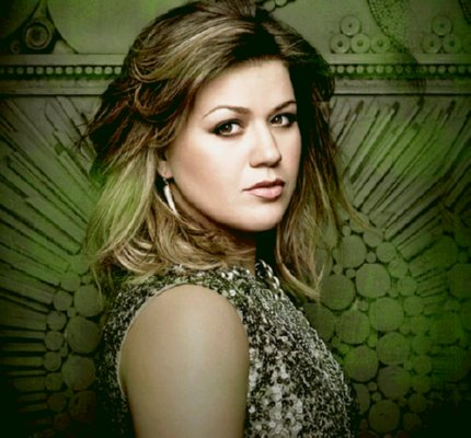 Kelly Clarkson in a sparkly dress against a green background
