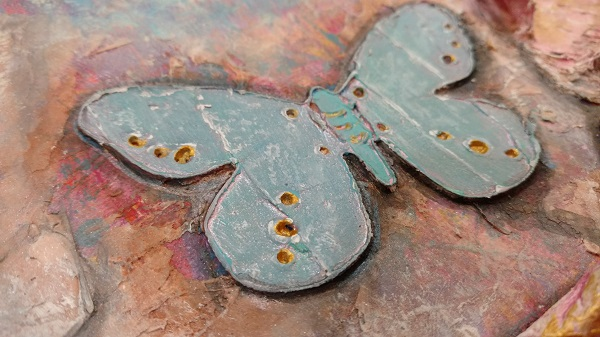 close up view of a blue butterfly on the art piece