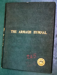 "Cover of the Armagh - dark green background with ""Amagh Hymnal"" and the stamp of the Catholic Truth Society of Ireland in gold-leaf lettering"