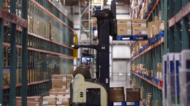 A Walmart worker operates a forklift at a distribution center