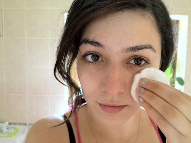 A person using toner on a cotton pad on their face