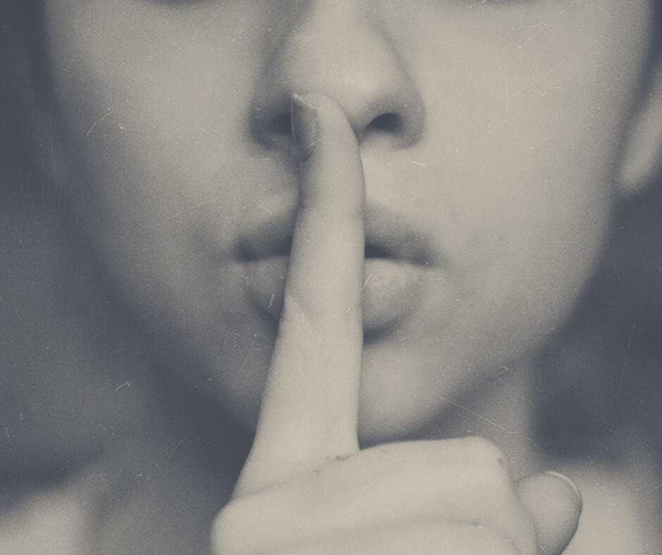 A woman puts her finger over her lips, signifying silence.
