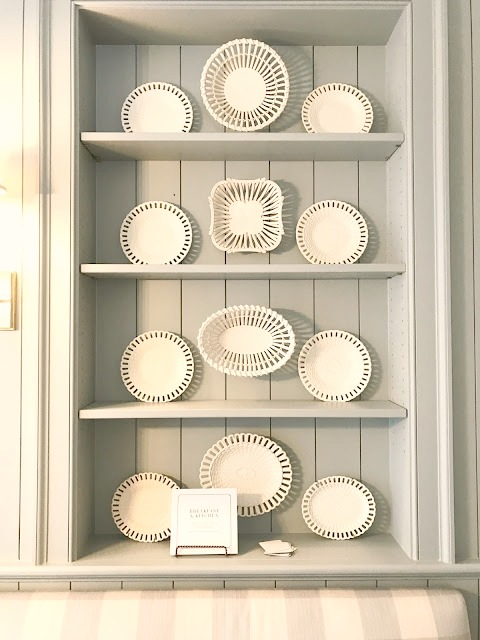 Lace creamware plates on blue painted shelves in traditional kitchen at Southeastern Designer Showhouse 2017