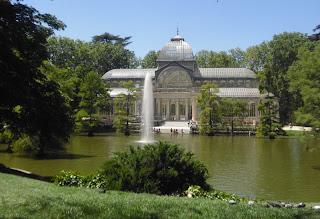 El Palacio de Cristal, con el lago delante, en el centro surtidor de agua y rodeado de vegetación