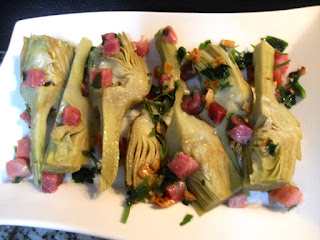Presentación final en plato de las alcachofas con jamón