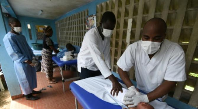 Medical staff use massage to treat a child with breathing problems in Abidjan