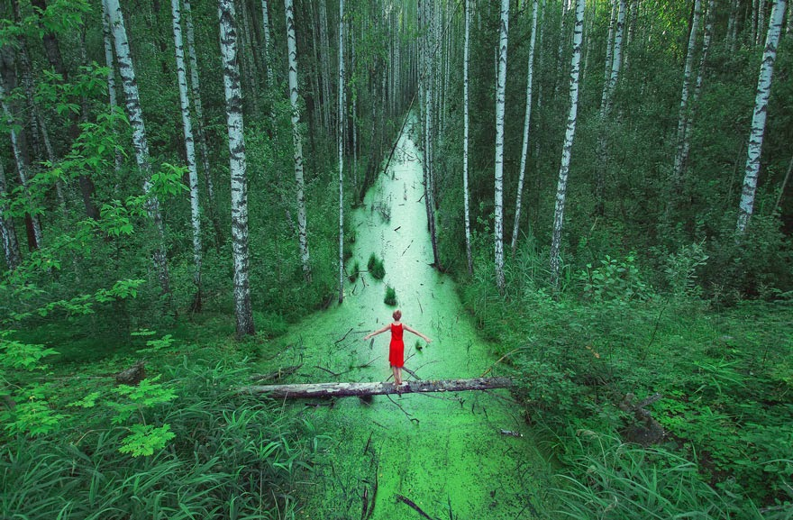 Her red dress stands out, but her body remains small amongst this overgrow forest in Belarus. - Tiny Humans Lost In The Majesty Of Nature