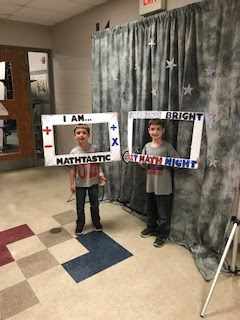 Two boys in t shirts and jeans posing with math signs