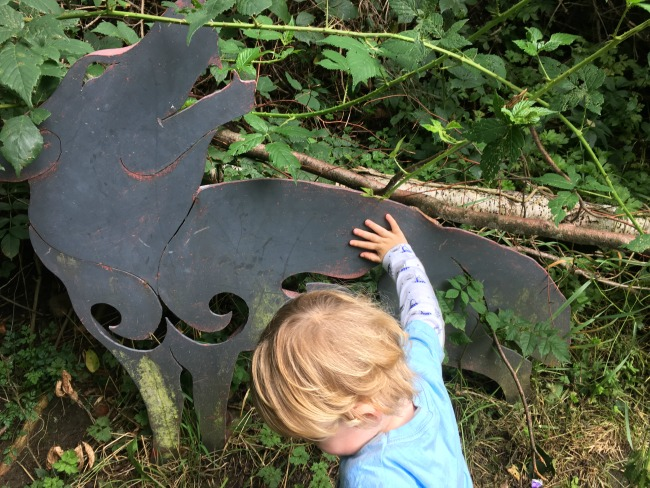 toddler-touching-metal-wolf-sculpture