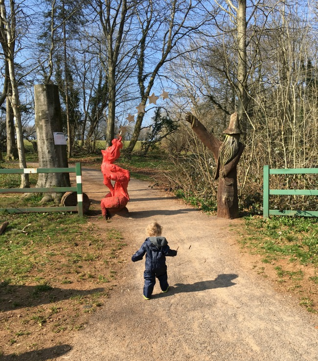 The Fforest Fawr Sculpture Trail Entrance of carved dragon and wizard and toddler running towards it.