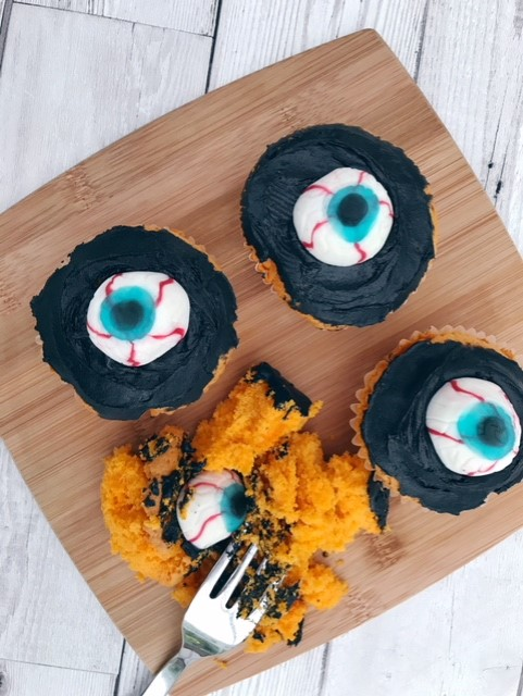 Cup cakes laid out on a board with orange sponge, black icing and an eyeball sweet on top of it