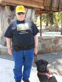 William stands beside his guide dog Leif, a black Labrador retriever. William wears a yellow hat, t shirt and jeans. They stand beside a wooden cabin coffee shop in Parkfield California.