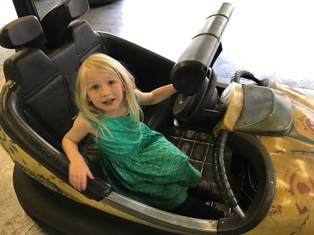 A dodgem car with a girl in a green dress sitting in it