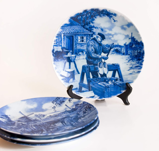 A few plates in Delft showing Dutch scenes, including a wooden shoe maker.
