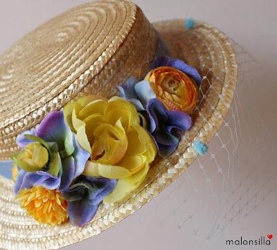Imagen que muestra en detalle el canotier, sombrero de copa baja, modelo Argentina con tapafeas de plumeti y flores en amarillo y azul claro.