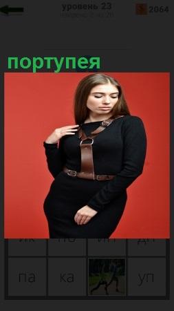 На красном фоне стоит девушка в черном платье и портупея на ней