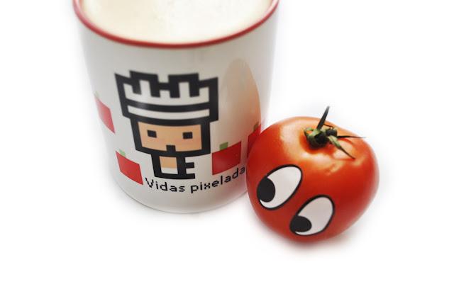 Un tomate con pegatinas de ojos, mira una taza de vidas pixeladas, el logo de vidas pixeladas en un bebé hecho con cuadrados con sombrero de cocinero, rodeado de cuadrados rojos con un cuadrado verde pequeño encima, simulando ser tomates.