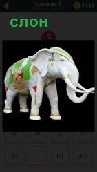 Фарфоровый слон разукрашенный по бокам цветной краской и стоит на столе